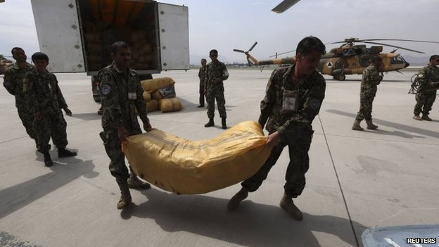 Afghan National Army troops load supply for survivors of the Badakhshan landslide onto a helicopter in Kabul, 3 May 2014