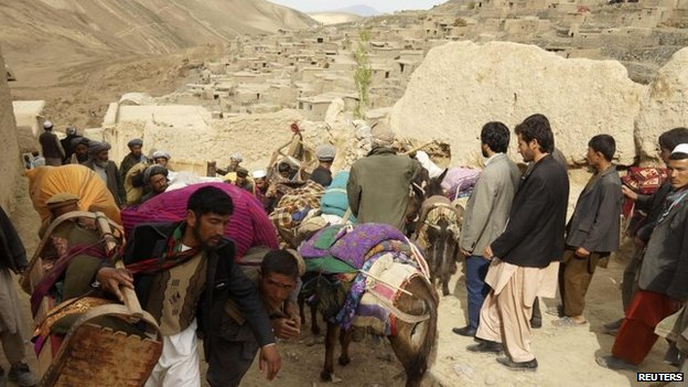 People walk with their belongings near the site of a landslide at Badakhshan province, 3 May 2014