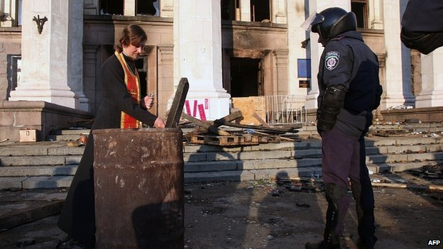 A policeman looks at an Orthodox priest preparing for a service outside the burned trade union building in the southern Ukrainian city of Odessa