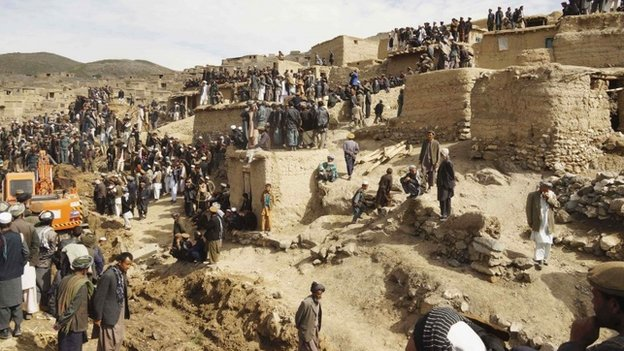 Afghan villagers gather at the site of a landslide at the Argo district in Badakhshan province,