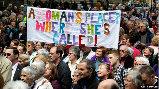 "A crowd marching with a banner saying: ""A woman's place? Where she's called."""