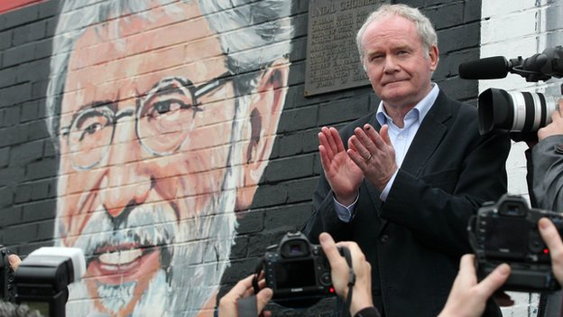 Martin McGuinness applauds after speaking at a rally