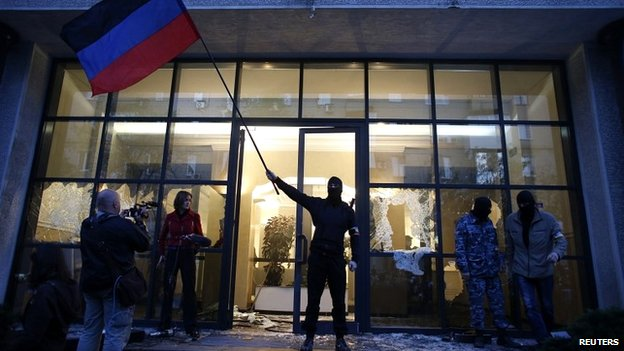 A pro-Russia protester waves a Donbass flag after storming a governor's offices in Donetsk - 3 May 2014