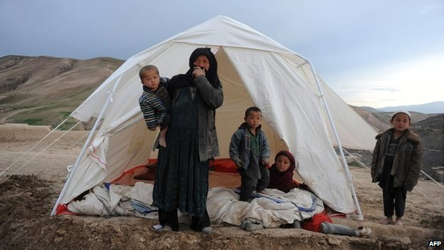 An Afghan woman with her children stands near her tent at the site of a landslide at the Argo district in Badakhshan - 3 May 2014