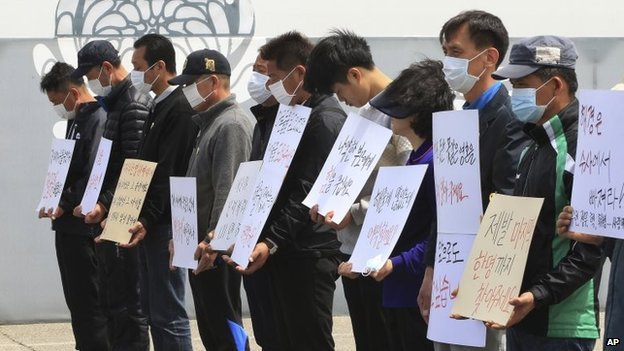 Family members of passengers aboard the sunken ferry Sewol stand to protest delays in the search operation at a group memorial altar in Ansan, South Korea, 4 May 2014