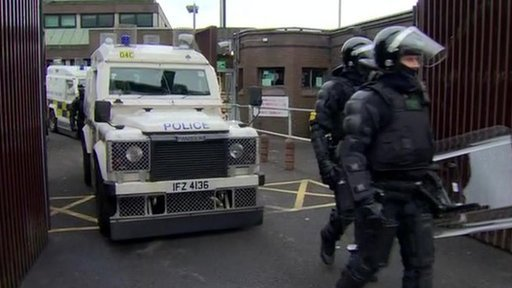 Police officers and vans emerging from Antrim PSNI base