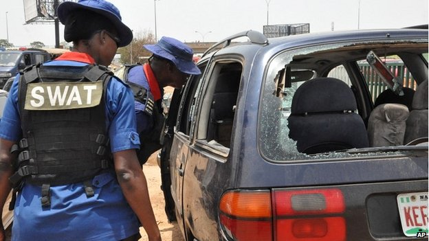 Security officers inspect a damaged car after a blast in Abuja - 2 May 2014