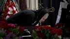 A woman leans over the coffin of regional parliament member Vyacheslav Markin, in Odessa, Ukraine
