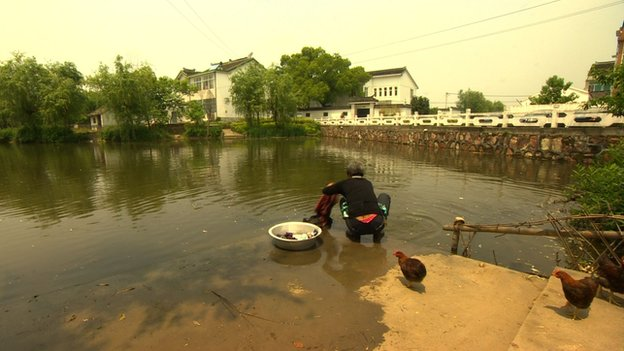 A woman washing clothes in the pond in Zhou Yongkang's home village of Xiqiantou, in Jiangsu province