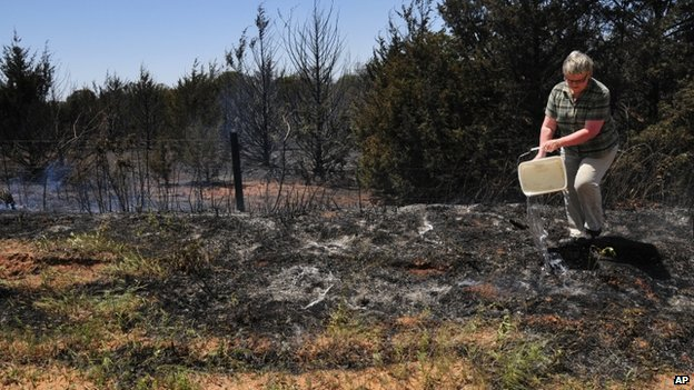 Wilma Rogers pours water on a hot spot across the road from her home in hopes of keeping the fire from spreading in Guthrie, Oklahoma 5 May 2014