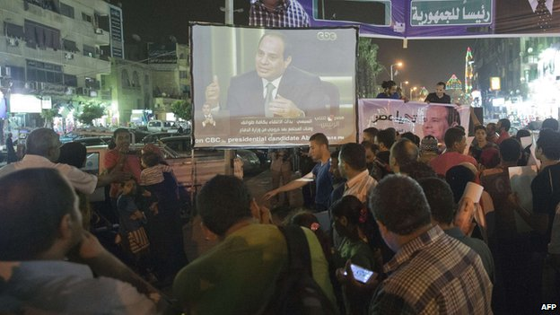 Egyptians watch Egypt's former army chief Abdel Fattah al-Sisi on a screen from the street in downtown Cairo on May 5