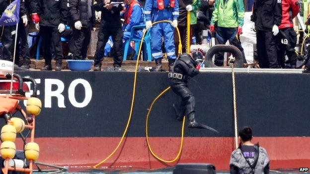 "A diver jumps into the sea to search missing passengers at the site of the sunken South Korean ferry ""Sewol"" off Jindo on April 25, 2014."