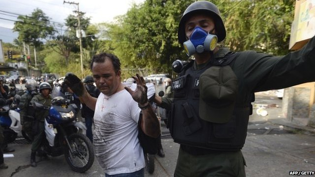 Venezuelan National Guard member arrests an anti-government activist