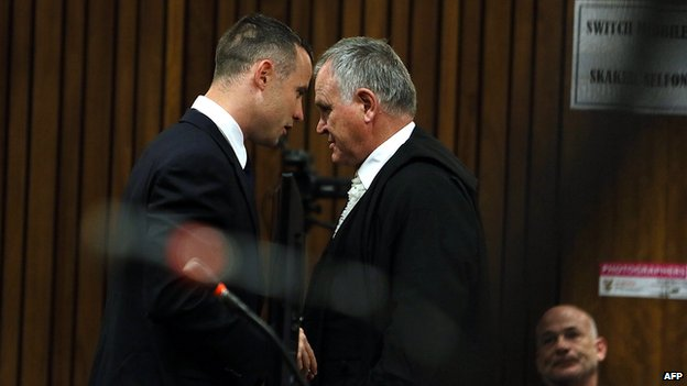 South African Paralympian sprinter Oscar Pistorius (L) consults with his defence lawyer Barry Roux during his murder trial at the high court in Pretoria on 6 May 2014.