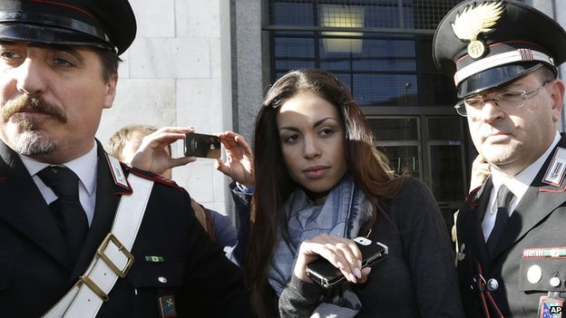 Karima el-Mahroug's is escorted outside a Milan court by two Carabinieri police officers after giving her testimony at the trial in Milan (May 2013)