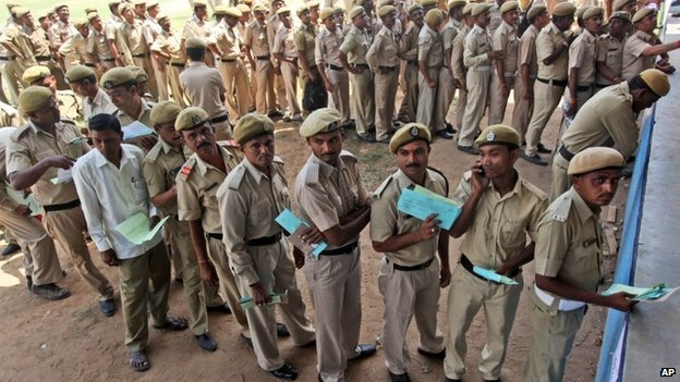 Indian home guards stand in queues in Ahmedabad on 23 April 2014 to vote before heading off to their assigned polling station