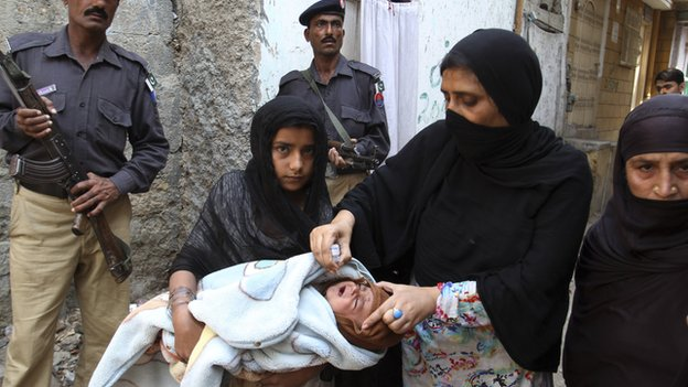 Pakistani policemen stand guard as a health worker gives a child a polio vaccine in Karachi, Pakistan, on 9 March 2014.