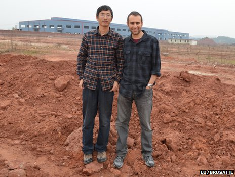 Prof Junchang Lu and Dr Steve Brusatte at construction site where dinosaur fossil discovered
