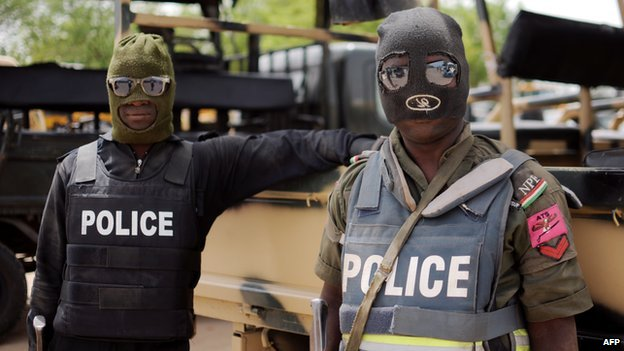 Nigerian police part of the joint forces in Borno state pose prior to a patrol in former Boko Haram headquarters in Maiduguri on 5 June 2013