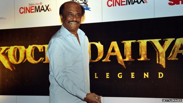 Rajinikanth in front of a poster for his new film