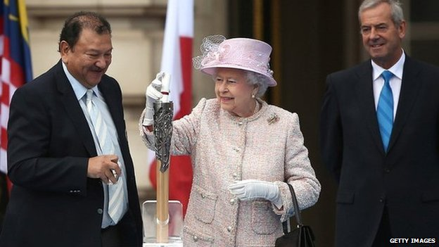The Queen places her message inside the intricate head of the baton, watched by Commonwealth Games Federation president Prince Imran Tunku and Lord Smith of Kelvin, who chairs the Glasgow 2014 Organising Committee.