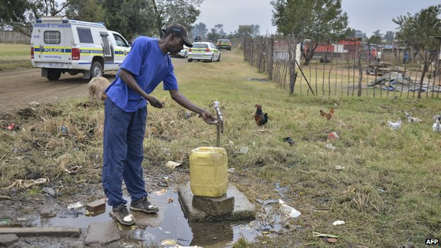 A man takes water while South African police officers patrol aboard vehicles in the restive township of Gugulethu