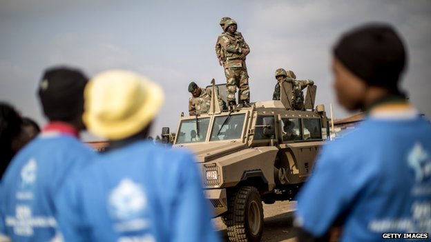 Electoral commission officials look at an army truck parked outside a polling station in Bekkersdal on May 6, 2014