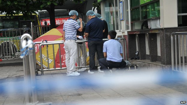 Investigators inspect the scene after a knife attack on the square of Guangzhou railway station in Guangzhou, in southern China's Guangdong province on 6 May 2014