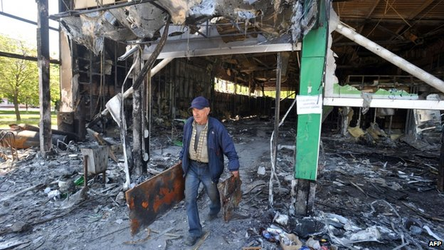 A man carries fragments of metal constructions from Privat Bank building burned by pro-Russian activists in Mariupol, 7 May
