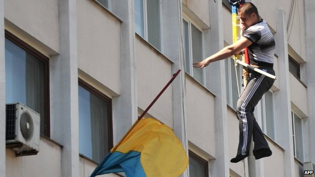 A pro-Russian activist throws down a Ukrainian flag outside the city hall building in Mariupol, 7 May