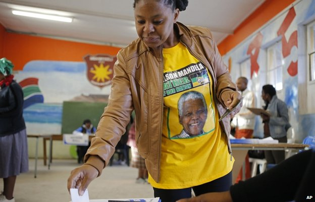 A woman in a T-shirt with former South African President Nelson Mandela printed on, casts her ballot in the township of Nyanga on the outskirts of Cape Town, South Africa
