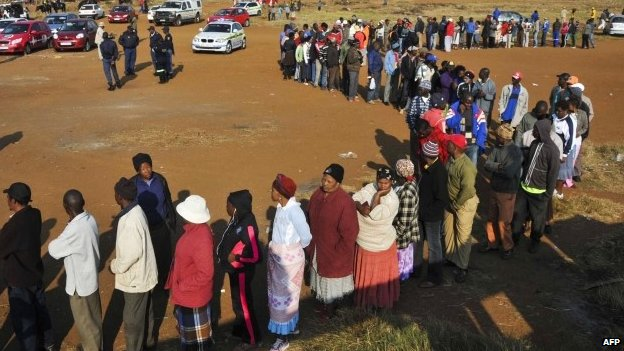 People queue at the entrance of a polling station to cast their ballot as part of the general elections, on 7 May 2014 in Bekkersdal, South Africa