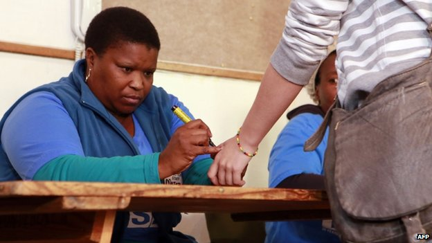 A scrutiniser marks the thumb of a voter for the general elections at a polling station on 7 May 2014 at a polling station in Cape Town, South Africa