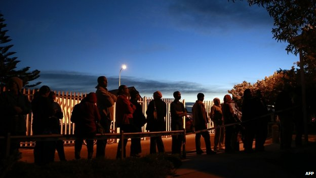 People queue to vote for the general elections on 7 May 2014 in front of a polling station in Cape Town