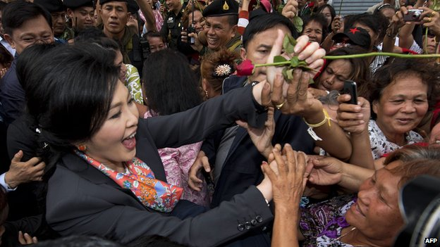 Ousted Thai Prime Minister Yingluck Shinawatra (L) receives a rose from supporters in a suburb of Bangkok on 7 May 2014.