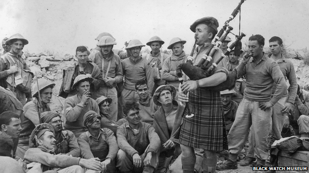 Pipe Major Rab Roy (Black Watch regiment), also known as the Piper of Tobruk, plays for some of the wounded at an aid post after an attempted breakout from the besieged fortress of Tobruk.