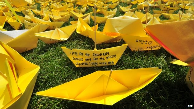 Messages written on yellow paper ships forming the shape of a heart are seen at a memorial for victims of the ferry disaster in Seoul on 7 May 2014