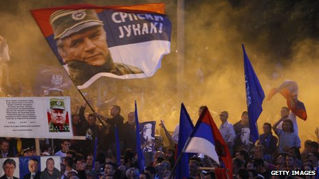"Supporters of Ratko Mladic wave flags with his picture and reading in Serbian ""Serbian hero"" during a rally organized by the ultra-nationalist Serbian Radical Party in front of parliament in Belgrade on 11 May 29"
