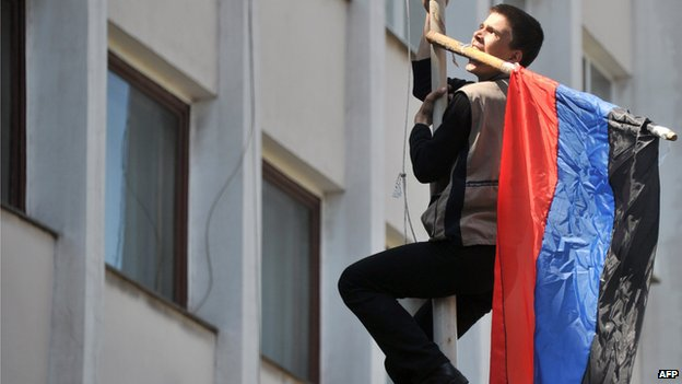 Pro-Russian activist climbs flagpole outside city building in Mariupol on 7 May 2014