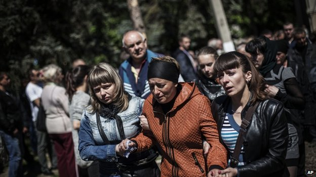Relatives and friends of pro Russia gunmen killed in clashes with the Ukrainian army on Monday cry after the funeral of several pro Russia gunmen and a civilian in Sloviansk