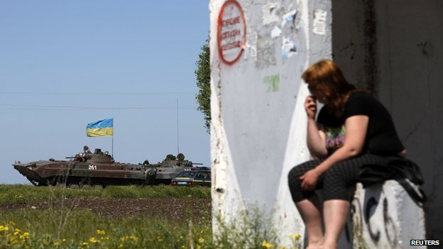 A woman looks at a Ukrainian armoured personnel carrier at a checkpoint in Mariupol, eastern Ukraine