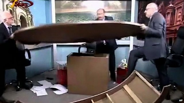Journalists shoving broken desk