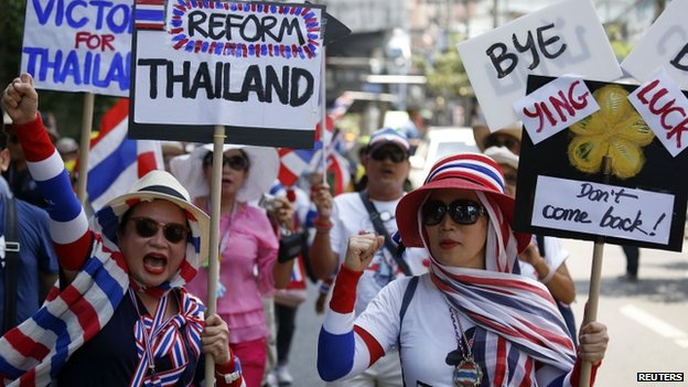 Anti-government protesters carry signs against ousted Prime Minister Yingluck Shinawatra as they march in central Bangkok, 8 May 2014