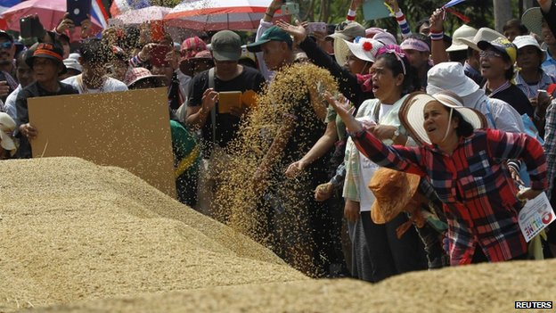 Farmers rearrange a pile of rice during a rally in Bangkok, 11 March 2014