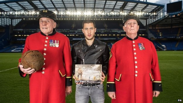Chelsea and Belgium footballer Eden Hazard with Chelsea pensioners Steve Lovelock (left) - holding a football - and Dave Thomson (right) at Stamford Bridge football ground, London