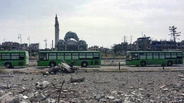Buses carrying rebels from the Old City of Homs travel through the Khalidiya district (7 May 2014)