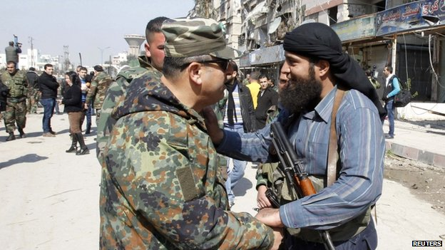 A Syrian rebel chats with an army officer after a local ceasefire is agreed in Babila, south-eastern Damascus (17 February 2014)