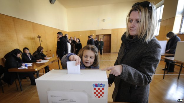 Little girl casts her mother's ballot in the Croatian referendum on EU membership on 22 January 2012