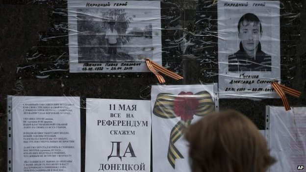 "A woman reads the piece of paper reading ""May 11, all on a referendum, say yes Donetsk republic"" on the monument of former Soviet leader Vladimir Lenin in the centre of Sloviansk"