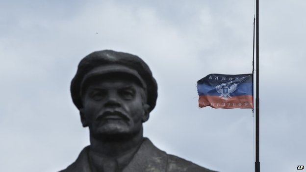 A Donetsk Republic flag on top of an administration building next to the monument of former Soviet leader Vladimir Lenin in the centre of Sloviansk